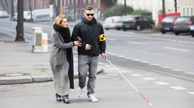 Visually impaired man walking across a road with a white stick and support from a woman