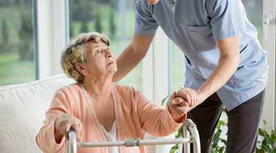 Elderly lady being help up to her walking support frame
